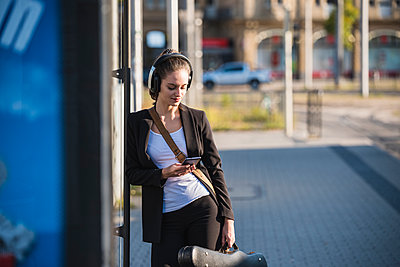 Young woman with headphones and cell phone at tram station - p300m2059611 von Uwe Umstätter