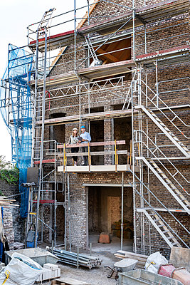 Mature professional team working while standing in balcony at construction site - p300m2257123 by Peter Scholl