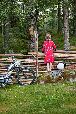 Girl standing near wooden fence and looking away - p312m1114131f by Sara Winsnes