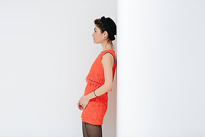 Female model in an orange dress leaning against a white wall. - p686m1124872 by Paul Tait
