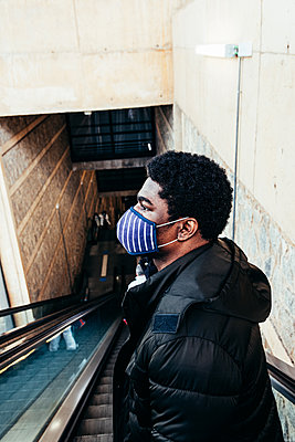Portrait of black afro american boy with face mask going down escalator. - p1166m2254949 by Cavan Images