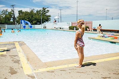 Litte Girl in Swimsuit at Swimming Pool's Edge - p1238m1042098 by Amanda Voelker