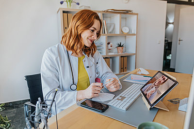 Doctor listening to patient on video call over digital tablet while sitting at office - p300m2267730 by Mareen Fischinger