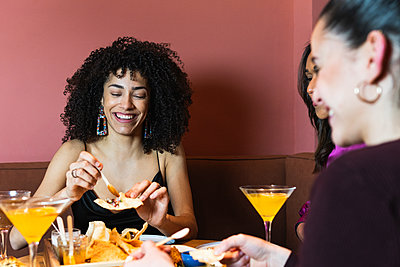 Smiling woman having appetizer with friends in restaurant - p300m2286795 by NOVELLIMAGE