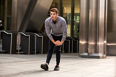 Young runner stretching on pavement, London, UK - p429m2075352 by Tom Dunkley