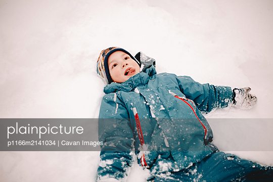Happy boy sticking out tongue while lying in snow in winter - p1166m2141034 by Cavan Images