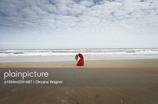 Young red-haired woman in red dress bent over in despair against the waves of Atlantic Ocean - p1694m2291687 by Oksana Wagner