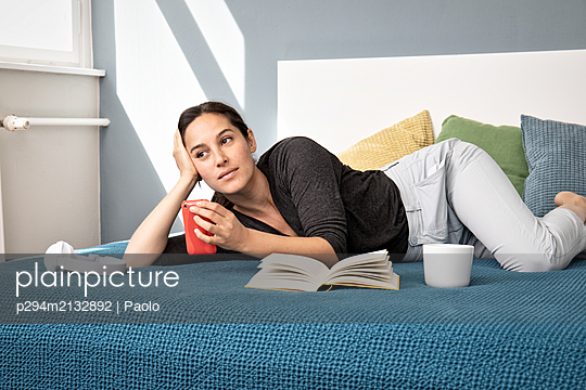 Young woman on bed chilling  - p294m2132892 by Paolo