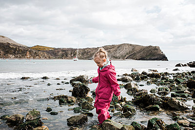 blonde girl walking on rocks at the beach at lulworth cove, England - p1166m2107146 by Cavan Images