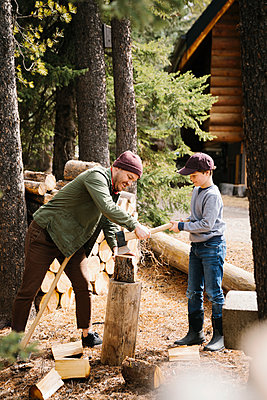 Father teaching son how to cut firewood outside cabin - p1192m2094148 by Hero Images