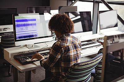 Male audio engineer working on digital editing screen - p1315m1422192 by Wavebreak