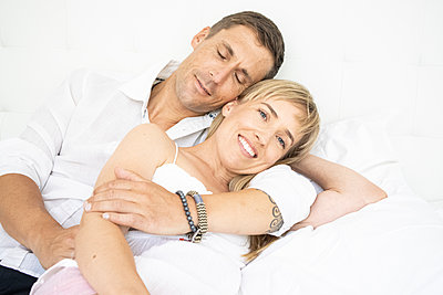 Happy couple cuddling on bed, portrait - p1640m2259617 by Holly & John