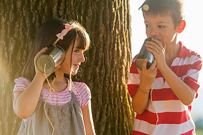 Little boy and girl playing with tin can phone in nature - p300m1140680 by ZoneCreative