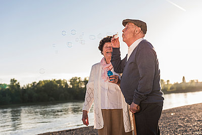 Senior man blowing soap bubbles on the beach at sunset - p300m1459754 by Uwe Umstätter