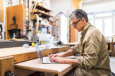 Mature male carpenter working on laptop in workshop - p300m2293685 by Eugenio Marongiu