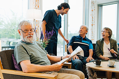 Portrait of retired senior man sitting with newspaper on armchair by friends and caretaker at elderly nursing home - p426m2149361 by Maskot