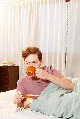Man drinking coffee in bed - p42917206f by Elke Meitzel