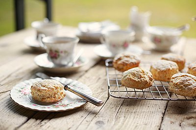Table with fresh baked scones and afternoon tea - p429m1046914f by Tim MacPherson