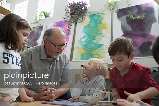 Senior volunteer and preschool students using digital tablet in classroom - p1192m1560209 by Hero Images