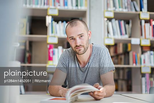 Student durchblättert ein Fachbuch in der Bibliothek - p1284m1452051 von Ritzmann