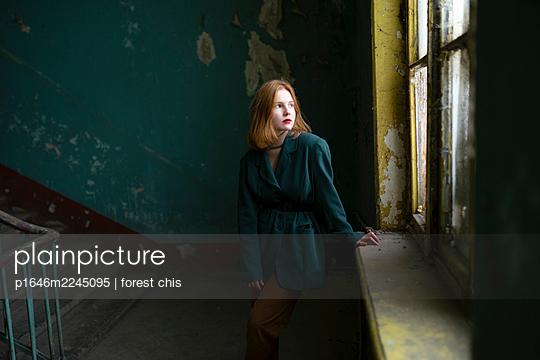 Teenager im Treppenhaus blickt aus dem Fenster - p1646m2245095 von Slava Chistyakov