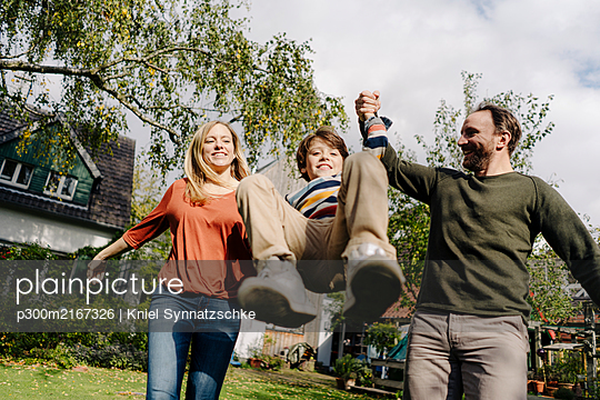 Parents swinging son, holding his hands - p300m2167326 by Kniel Synnatzschke