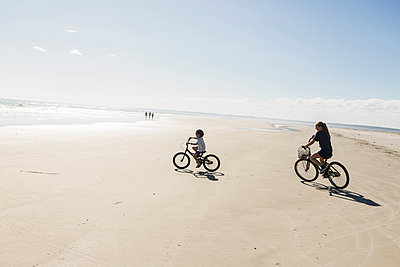 Two children cycling on an open beach, a boy and girl.  - p1100m2214461 by Mint Images