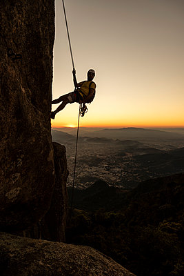 Man rappelling steep rocky mountain with beautiful dusk golden hour - p1166m2153314 by Cavan Images
