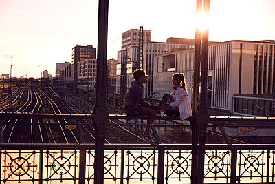 Germany, Munich, Young couple sitting on bridge, enjoying sunset - p300m1494784 by Sullivan