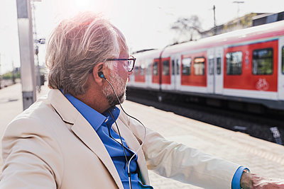 Mature businessman with earbuds sitting at train station - p300m1587243 von Uwe Umstätter