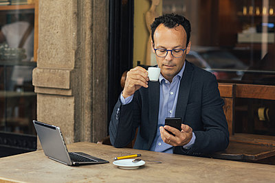 Businessman with laptop in a coffee shop looking at his smartphone - p300m2114032 by Alberto Bogo