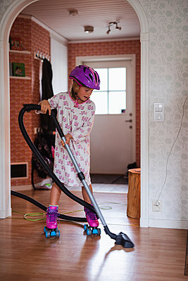 Girl vacuum cleaning on roller skates - p312m2091395 by Anna Johnsson