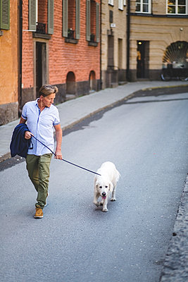 Full length of senior man walking with dog on road by buildings in city - p426m2046362 by Maskot