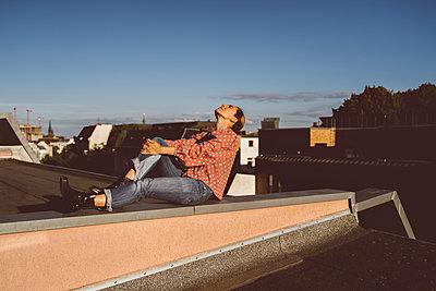 Frau entspannt auf Hausdach - p432m2203193 von mia takahara