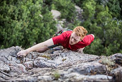 Caucasian man rock climbing - p555m1302115 by Mike Kemp