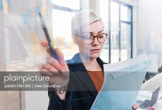Businesswoman working on document in office - p300m1581365 von Uwe Umstätter