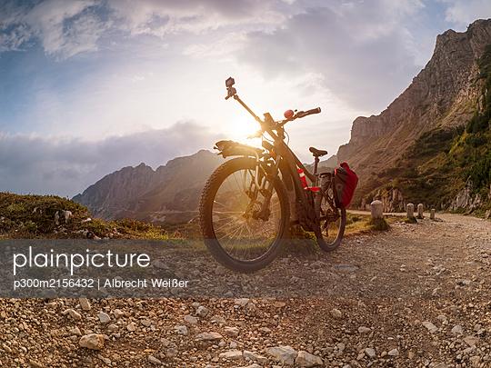 Italy, Trentino, Pasubio massif, Vicentine Alps, Strada degli Eroi and Strada degli Scarubbi, Electric mountain bike with camera on mountain road - p300m2156432 by Albrecht Weißer
