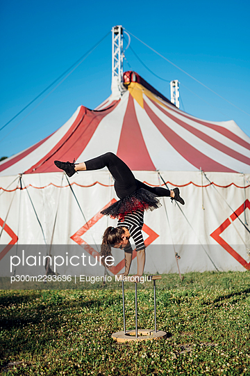 Female acrobat doing handstand on cane in front of circus tent - p300m2293696 by Eugenio Marongiu