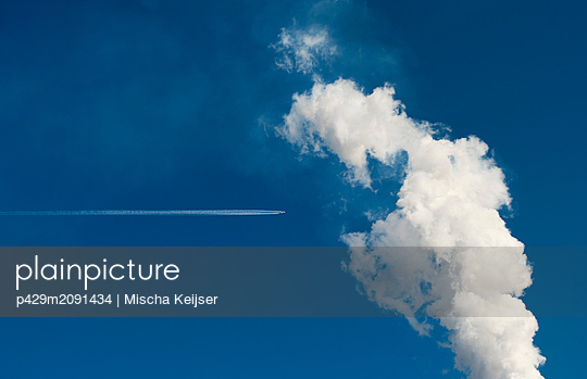 Smoke leaving chimney, contrail of passing plane - p429m2091434 by Mischa Keijser