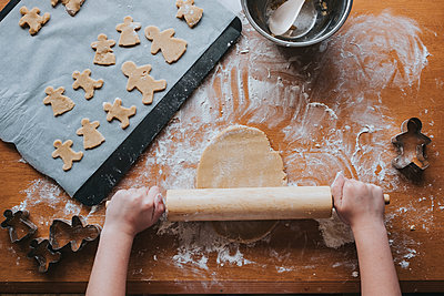 Looking down at young girl rolling out gingerbread dough - p1166m2137143 by Cavan Images