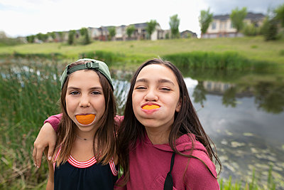Portrait playful girl friends with orange slice smiles - p1192m2009425 by Hero Images