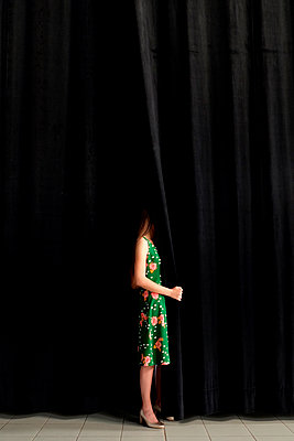 woman green dress black curtains of theater - p1521m2081628 by Charlotte Zobel