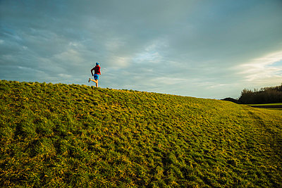 Germany, Mannheim, young man jogging in meadow - p300m1023039f by Uwe Umstätter