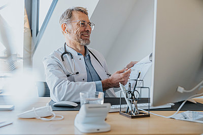 Mature doctor with document smiling at video call on computer in doctor's office - p300m2267713 by Mareen Fischinger