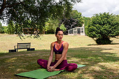 Woman practicing yoga in garden, taking a break on yoga mat - p429m2032216 by Image Source