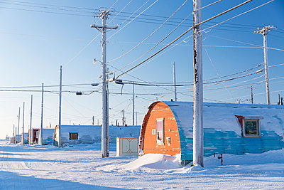 A row of powerlines stand beside Barrow Naval Base Quonset huts, Barrow, Arctic Alaska, Winter - p442m1033952 by Design Pics