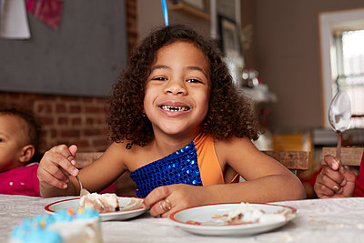 Mixed race girl eating cake at table - p555m1413152 by Granger Wootz