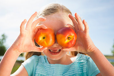 Caucasian girl holding fruit over eyes - p555m1453261 by Mike Kemp