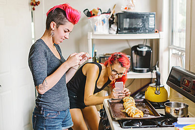 Two young women with pink hair taking smartphone photographs of stuffed baguette in kitchen - p924m1180288 by Lena Mirisola