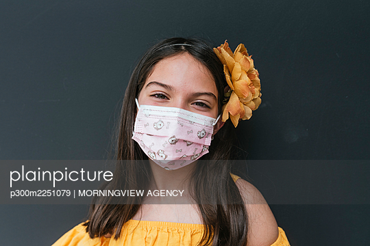 Close-up of girl wearing face mask against black background - p300m2251079 by MORNINGVIEW AGENCY